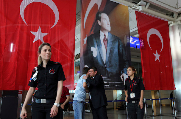 Men greet each other in front of Turkish flag and picture of modern Turkey's founder Mustafa Kemal Ataturk at Istanbul Ataturk airport, Turkey, following yesterday's blast